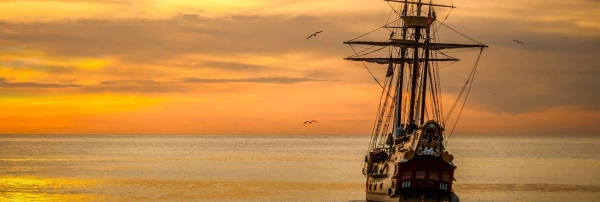 Sailing ship upon the sea at sunset