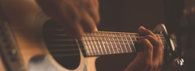 person strumming guitar with capo