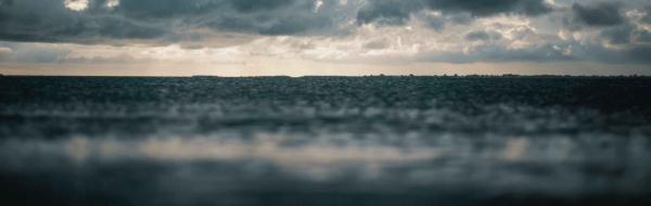 dark ocean beneath a cloudy sky