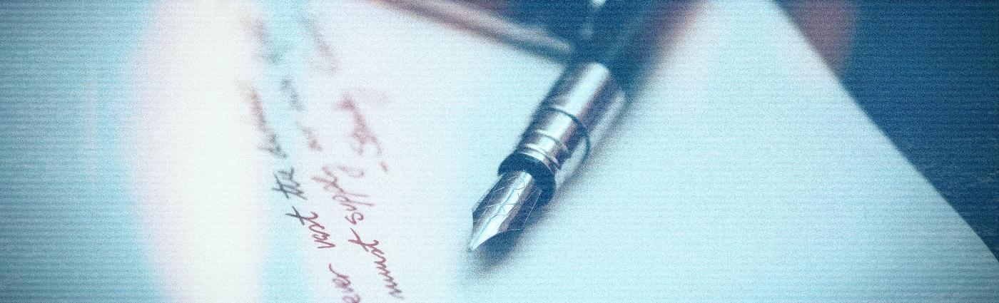 words written on paper beside an ink pen