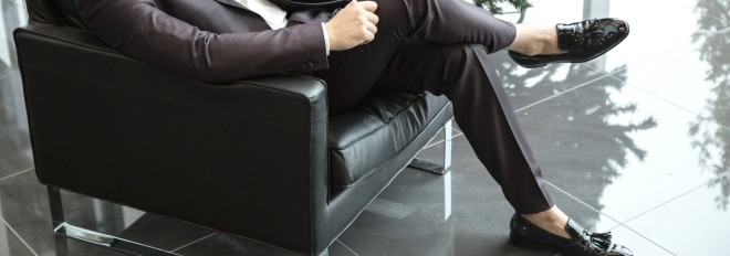 suited man in black leather chair