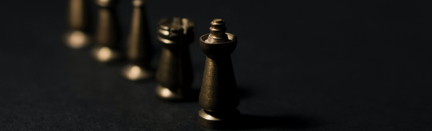 wooden chess set pieces set in a line on a dark background