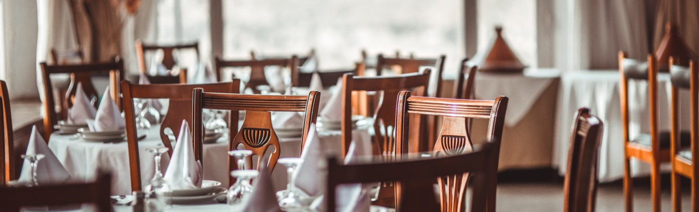 Dining tables and chairs topped with napkins and crockeryq